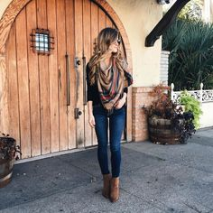 brighton the day styling jeans, brown booties, black tee, and plaid blanket scarf