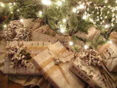 Newspaper wrapped Christmas gifts with burlap ribbons and paper roses. ALTERED ARTIFACTS