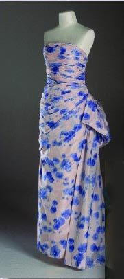 Designed by Catherine Walker. This strapless taffeta evening gown is adorned with blue flowers. Diana wore this famous gown, and danced with Charles at Melbourne in 1988. $50,600.00  Purchased by Suzanne King from Texas. Suzanne King founded Pink ribbons Crusade. Her husband Jess is owner of Cablevision of Marion County.