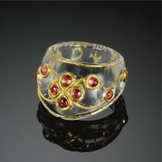 A gem-set rock-crystal archer's ring, India, 19th century of typical form, overlaid with gold wire and set with spinels with a central floral rosette surrounded by scrolling tendrils issuing buds. 3.5cm