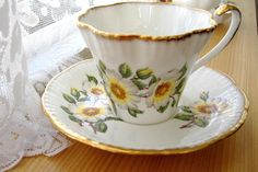 This is a Salisbury, England tea cup and saucer in a pretty pattern of dog roses on fancy ruffled white bone china with hand brushed gold trim with pattern number 3547. The cup is 2.85 high, the sauce