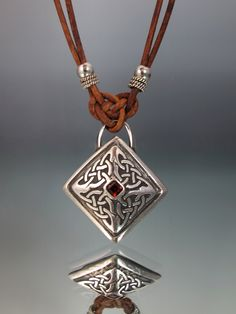 I made this pendant as a hollow form, in fine silver and a natural garnet set in the middle.  I put a Josephine knot on top for a bail. -  Lisa Barth