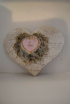 The puff paper mache heart was purchased from Michael's and then was decoupaged with wrapping paper. I then took a small wooden heard painted it and stamped love on it and glued eyelash fringe trim around the heart. Then the little heart was glued to the paper mache heart. Very easy