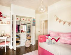 Fun girl's room features pink polka dot wallpaper on ceiling accented with white mesh chandelier illuminating pink velvet daybed dressed in pink velvet bolster pillows with white piping and pink sequins pillows atop white and pink striped rug.