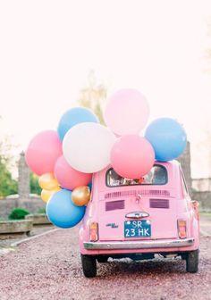 Carro rosa e balões coloridos