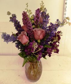 Another lovely lavender arrangement that has a lavender vase, tall purple gayfeather, and dark purple blues that had height and elegance.