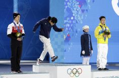 Men's free skate figure skating gold medalist Yuzuru Hanyu of Japan walks on to the podium as silver medalist Canada's Patrick Chan, left, a...