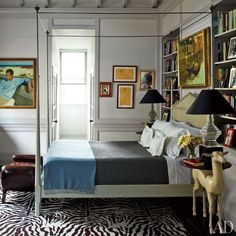 In the master bedroom is a large self-portrait of Rogers at a beach; the leather bench is from Vol. 1 Antiques, and the carpet is by Stark - Architectural Digest