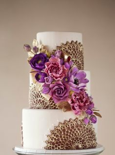 Purple & Gold wedding cake - Purple starburst lace molds brushed with gold & an arrangement of sugar flowers with gold leaves & ribbon (photo by Mark Davidson)