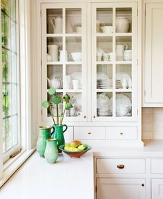 "Designer Sophie Burke included glass-front, Shaker-style cabinets in her parents' Vancouver kitchen to house her mother's china. ""We both love white dishes!"" Burke says. For more design and decorating"
