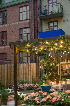 Sarah Widman outdoor styling for Cuprinol, spring trends 2015. Urban courtyard setting with dinner table under pergola on wooden terrace floor. Climbing greenery with roses and ivy on espalier. Scandinavian design classics. Urban gardening.