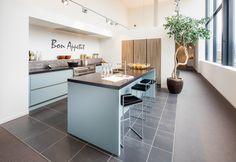Landelijke keuken met bar. Frisse kleuren in combinatie met houtlook hoge kasten. Nuva Keukens - Goed bedacht!