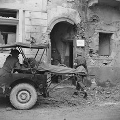 A patient is unstrapped from a jeep, which is fitted with litters for carrying the wounded. The patient is then carried into the operating theatre of a Field Surgical Unit (FSU) currently housed in a much bombed Italian prison, December 1943.