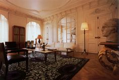 Yves Gastou's 9th arrondissement apartment.  A view of the salon with gracious proportions and glazed doors. The carpet is an Yves Gastou edition of an André Dubreuil design. The sofa is by Marc du Plantier, circa 1935. Both coffee table and the wall bracket are by Gilbert Poillerat in wrought iron and gold leaf; the heads are by Raymond Delamarre. —Lisa Lovatt-Smith, 1994  Photo by Deidi von Schaewen.