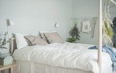 Una camera da letto simmetrica, con le pareti verdi, il pavimento in legno, piante, comodini bassi e un ampio letto in legno - IKEA