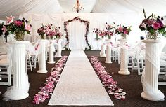 Rose petal aisle with fabric draped columns topped with floral arrangements.