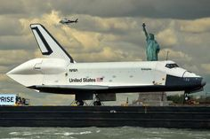 The space shuttle Enterprise is towed by barge past the Statue of Liberty in New York, on its way to the Intrepid Sea, Air and Space MuseumPicture: STAN HONDA/AFP/GettyImages Space Shuttle Enterprise, Uss Enterprise, Air And Space Museum, Space Program, Online College, Our Solar System, Space Exploration, The Life, Astronomy