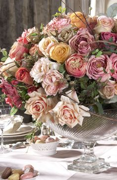 Roses mixed with leaves and branches in a wild, organic centerpiece