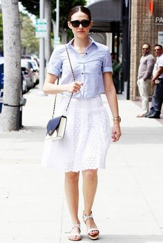 Emmy Rossum wears a striped blue button-down tucked into a white eyelet above the knee skirt, Loeffler Randall white tie sandals, and a Tory Burch color block bag