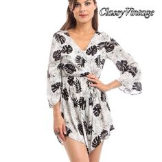 White and black leaf print romper. This is a fun little romper. It's 100% rayon and made in the USA. She runs true to size.. It comes in S,m and L. This is size Large The first Pic model is holding garment - this item does NOT cross over. It does have a drawstring waist and hook and eye for the shy. You will notice that model is wearing a cami under it. She is size XS and wearing a small. Boutique Dresses