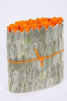 orange roses enclosed in leaves of lamb's ear. Key is orange string and roses  picture from Christian Tortu