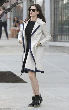 Anne Hathaway leather pleated kilt-like skirt and chic light beige coat which featured a dark navy lining.