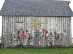 Home Again-Vintage Treasures: Not your everyday barn....a garden of old farm tools painted and hung on the side of the barn.