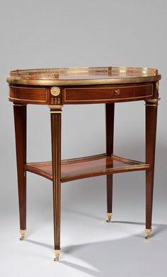 Belle table à écrire mécanique en acajou, de forme ovale, ouvrant à un grand tiroir contenant deux tiroirs et une tablette, libérant par un mécanisme deux autres tiroirs pivotant de chaque côté, le plateau surmonté d'une galerie reposant sur quatre pieds en gaine à cannelures réunis par une tablette d'entretoise à galerie ; pieds dévissables. Par David Roentgen, vers 1785-1790 Hauteur : 77 cm - Largeur : 73,5 cm Profondeur : 50 cm