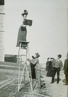 Jessie Tarbox Beals, first published female photojournalist in the US, precariously standing on a ladder, with a very large and heavy camera.