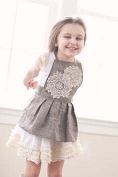 For that classic, nostalgic look of magical childhood, the Titania Apron Pinafore in charcoal grey is a must-have piece.   The front bib features a crochet doily, most sourced ...