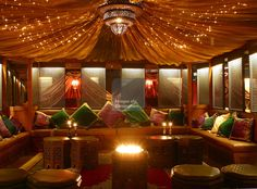 Moroccan tent and furnishings with traditional North African designs, including cushions, wooden screens