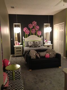 Yo quiero que un dormitorio de mi hija tenga una cama y los paredes negro con flores rosa y la sofá con tres almohadónes y dos espejos con los luces.