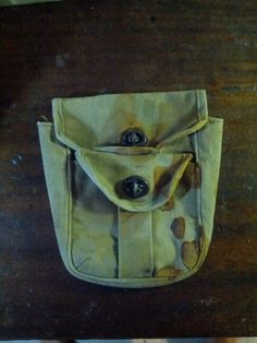 Small canvas pouch with metal fasteners. Rust stained
