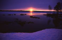 Sunset by lake during winter in Kuusamo, Finnish Lapland