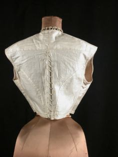 Chemisette, back, circa 1850, white moire, waistcoat shaped and boned laced at back. Black silk buttons, neck trimmed with lace threaded with black velvet ribbon, National Trust Collections.