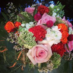 Orange and pink bouquet; stock, roses, sedum, thistle and wax flower