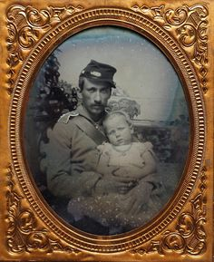 Early sixth plate ruby ambrotype of a father holding his young daughter. He's dressed in a grey uniform and still retains his cartridge box while he cradles his daughter in his lap.