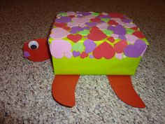 """Turtle Valentine box 2011. Small shoe box covered in green wrapping paper, cardstock for head tail and flippers, foam sticky hearts for the """"shell,"""" and google eyes."""