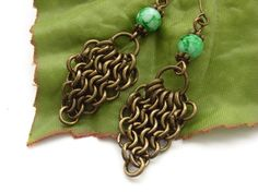 Chain maille triangle earrings with green glass beads in a lush antique bronze vintage tone. These earrings are for someone who likes to make a statement, and have a touch of goth, emo chic about them. The glass beads are approximately and the over. Blue Forest, Triangle Earrings, Chainmaille, Glass Beads, Bronze, Chic, Antiques, Bracelets, Green