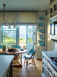 S. R. Gambrel collaborated with Robert A.M. Stern Architects on a home in East Quogue, New York. Steven Gambrel found the room's vintage chandelier in Paris; the table is made of reclaimed oak | archdigest.com