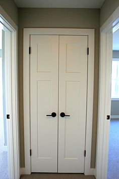 Craftsmen style painted white interior doors with Schlage Lattitude oil rubbed bronze handles and painted white woodwork.
