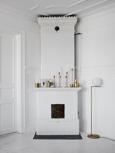 vintage fireplace with brass decorations and mix of candle holders. Perfection in White, Brass and Dark Hues by Lotta Agaton - NordicDesign - Flos floor lamp in brass