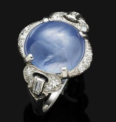 An Art Deco star sapphire and diamond ring, 1920s  The oval-shaped cabochon star sapphire, set within a diamond-set engraved partial surround, the pierced diamond-set shoulder of buckle motif, with baguette-cut diamond accents, mounted in platinum, sapphire weighing approximately 6.00-8.00 carats, diamonds approximately 0.25 carat total