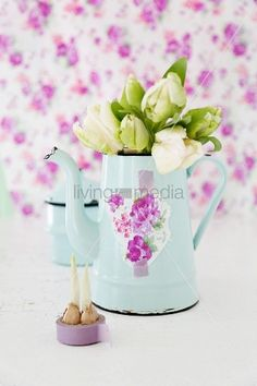 Bouquet of white tulips in nostalgic, pale blue coffee pot arranged against lilac background