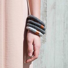 This woolen bracelet is an essential accessory for any wardrobe. It feels soft and warm against the hand and is made out of fine quality wool blend with a small shiny copper detail. The woolen feeling