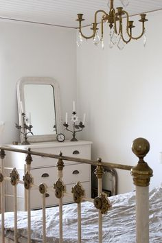 Vintage iron bed, lighting with crystals, dresser with vintage bin pulls