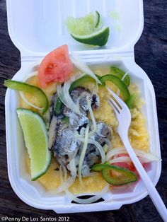 A Traditional Bahamian Breakfast Dish : Grits with sardines, sliced onion, green pepper and tomato with lime on top.