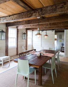 Exposed beams cover the ceiling of a country kitchen in upstate New York | wood tones, white walls + turquoise chairs