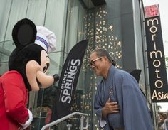 Mickey Mouse and Chef Masaharu Morimoto bow in celebration of the opening of…