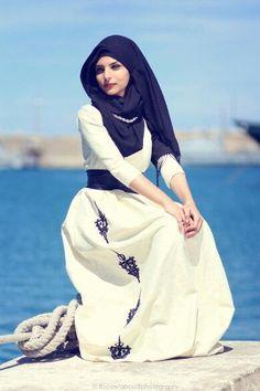 Dress panjang warna broken white dipadukan dengan hijab hitam, tampak elegan.